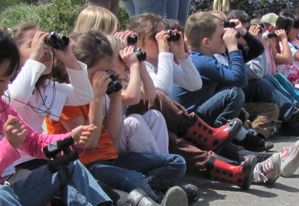 Discover the Flyway Kids with binoculars on curb